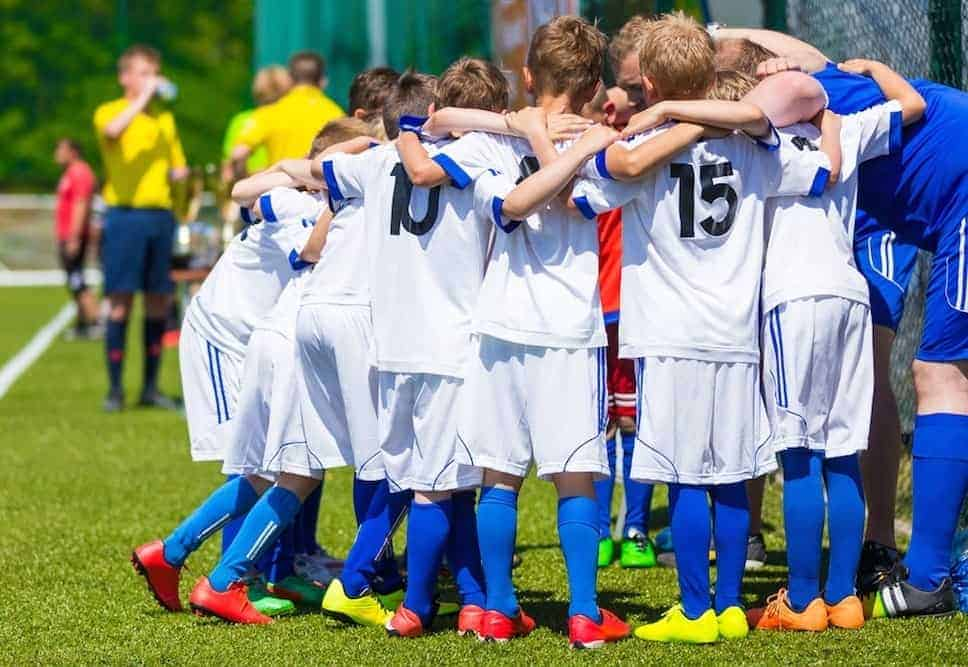 Boys on a youth soccer team in a huddle before the game.