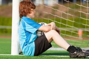 Sad boy leaning against a soccer goalpost.