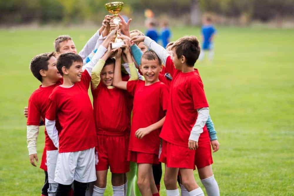 A group of boys on a soccer team hoisting a trophy in the air.